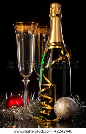 Glasses of champagne with bottles and christmas balls - stock photo