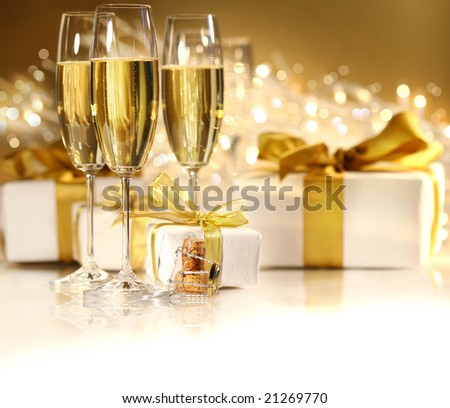 Glasses of champagne with gold ribbon gifts
