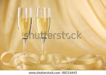 Glasses of champagne with golden ribbon. - stock photo