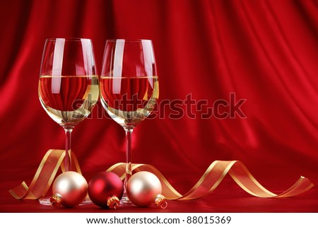 Glasses of champagne with golden ribbon and balls on festive background. - stock photo