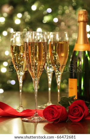 Glasses of Champagne with red roses ready to celebrate - stock photo