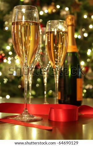 Glasses of champagne with ribbon against defocus Christmas Lights - stock photo