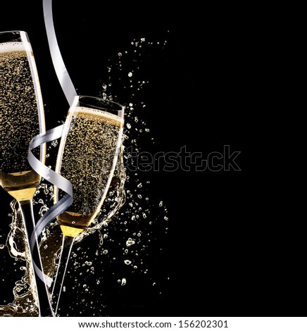 Glasses of champagne with splash, isolated on black background - stock photo