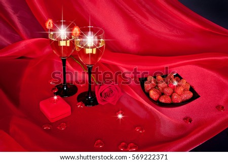 Glasses of champagne with strawberry and gift box, red roses and jewelry on black background. Valentine's Day. Red black still life.