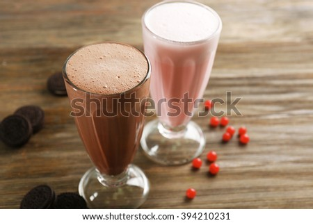 Glasses of chocolate and fruit milkshakes with berries and cookies on wooden background - stock photo