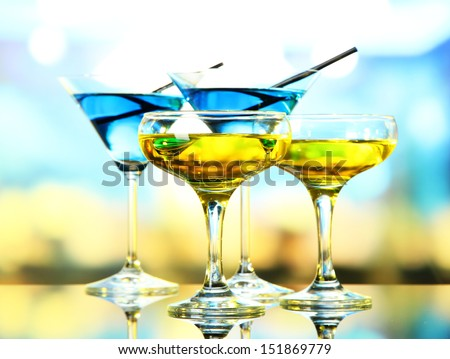 Glasses of cocktails on bright background - stock photo