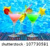 Glasses of cocktails on table on blue sea background - stock photo