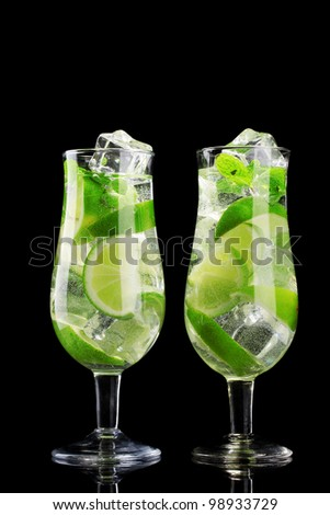 glasses of cocktails with lime and mint on black background - stock photo