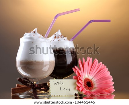 glasses of coffee cocktail and gerbera flower on brown background - stock photo