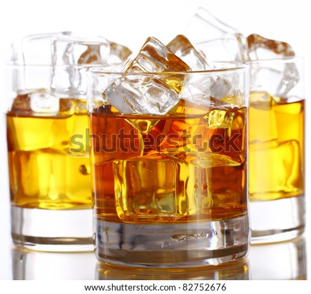 Glasses of cold whiskey with ice isolated over white
