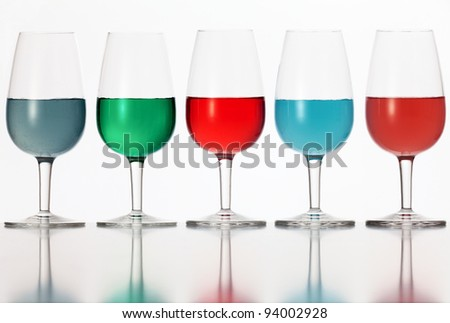 glasses of colored liquid photographed on a white background