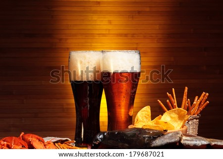 Glasses of dark and light beer with cips and snacks - stock photo