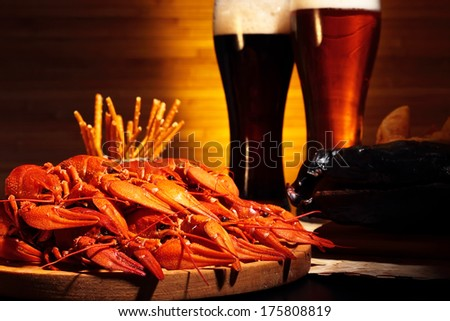 Glasses of dark and light beer with crawfish and smoked fish - stock photo