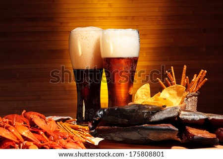 Glasses of dark and light beer with crawfish, chips and snacks - stock photo