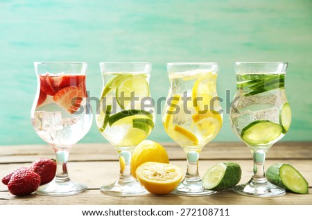 Glasses of different home made freshness healthy vitamin-fortified water on wooden table - stock photo