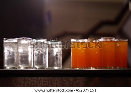 Glasses of drinking water and orange juice