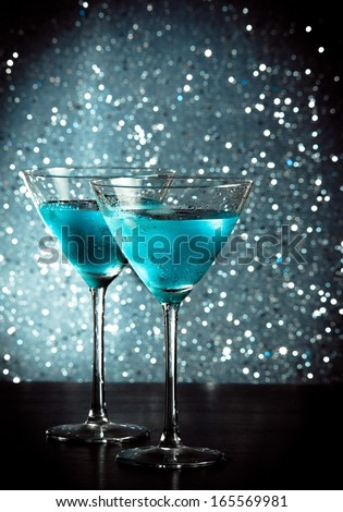 glasses of fresh blue cocktail with ice on blue tint light bokeh background on bar table - stock photo