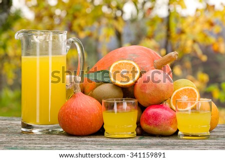 glasses of juice and lots of autumn fruits on wooden table, outdoor - stock photo