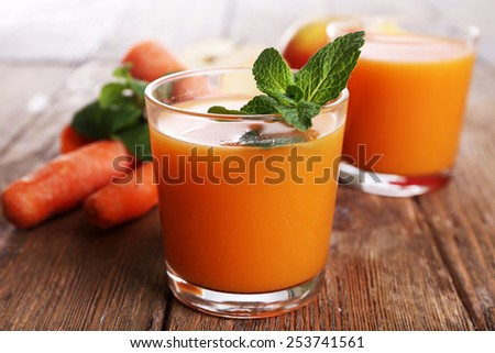Glasses of juice with apple and carrot on wooden table close up