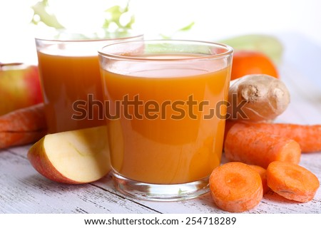 Glasses of juice with apple and carrot on wooden table close up - stock photo