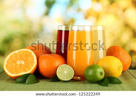 Glasses of juise with leafs and fruits on table on bright background - stock photo