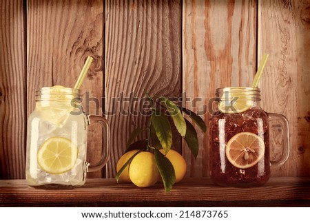 Glasses of lemonade and sweet tea with lemons on a ledge in front of a rustic wooden kitchen wall. The mason jar style glasses have handles and drinking straws. Instagram Style with vignette. - stock photo