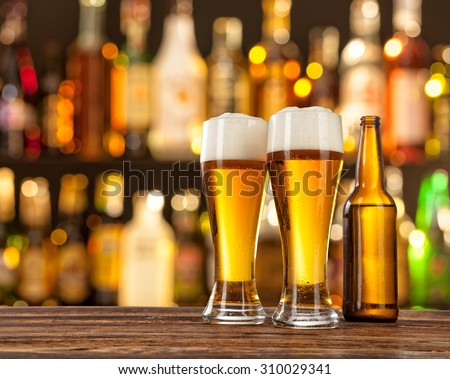 Glasses of light beer served on wooden desk. Bar on background