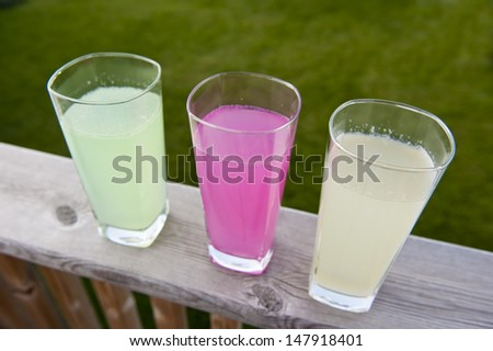 Glasses of limeade, pink lemonade and lemonade outside