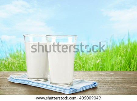 Glasses of milk on wooden table against grass and blue sky background
