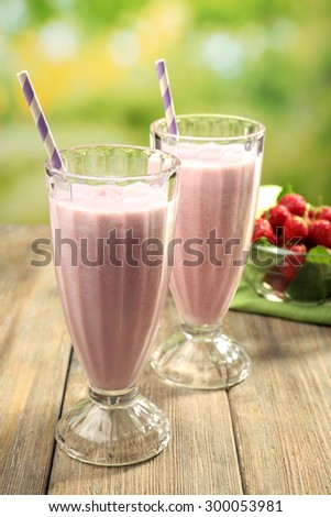 Glasses of milkshake with strawberries on bright background