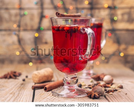 glasses of mulled red wine with spices on a wooden table - stock photo