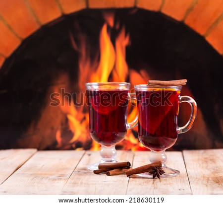 glasses of mulled wine on wooden table over fireplace - stock photo