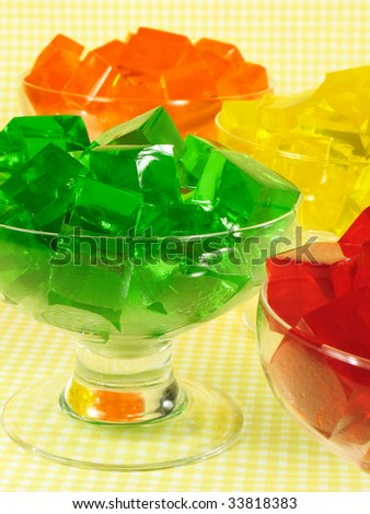 Glasses of orange, green, red, and yellow cubed gelatin. - stock photo