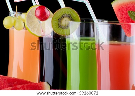 Glasses of organic juice made from fresh fruits and surrounded by fresh ones. Series about organic and healthy drinks. - stock photo