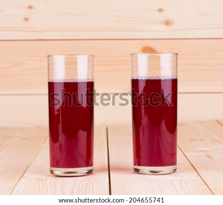Glasses of pomegranate juice on the wooden background - stock photo