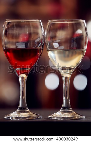 Glasses of red and white wine against blurred background