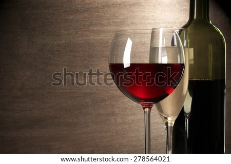 Glasses of red and white wine and bottle close-up on wooden background with copy space. Shallow DOF. - stock photo