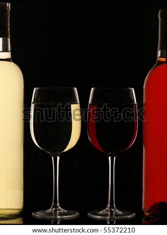 Glasses of red and white wine next to the wine bottles - stock photo