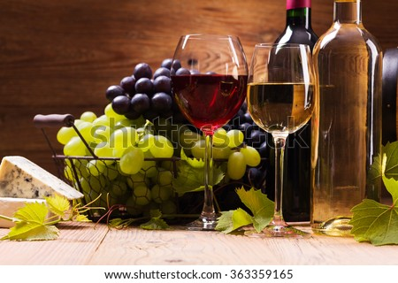 Glasses of red and white wine, served with grapes and cheese on a wooden background - stock photo