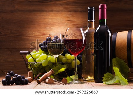Glasses of red and white wine, served with grapes on a wooden background - stock photo