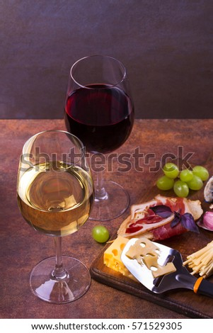 Glasses of red and white wine with smoked cheese, grape, prosciutto, garlic and bread. Wine and cheese still life. Food and drink concept