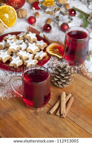 Glasses of red mulled wine on table with cinnamon sticks, Christmas decorations in background.