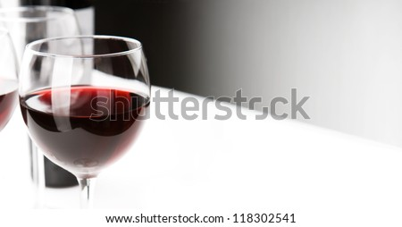 Glasses of red whine on white table cloth.