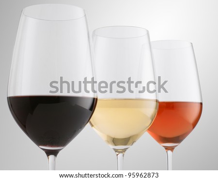 Glasses of red, white and rose wine (Shallow focus. Focus on white wine)
