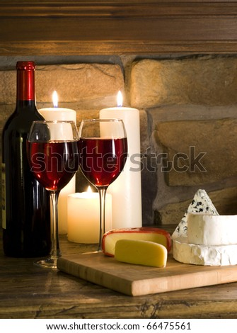 Glasses of red wine and cheese variates on a cheeseboard