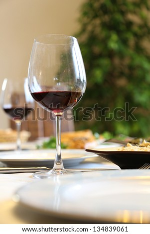 glasses of red wine and dinner on table - stock photo