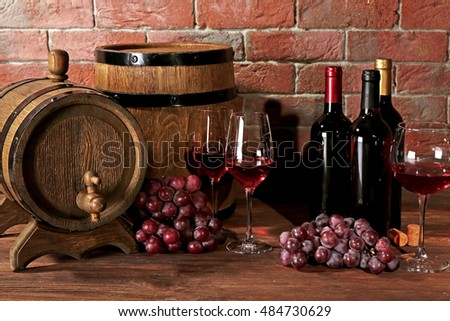 Glasses of red wine, grapes and wooden barrels on a brick wall background