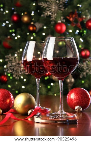 Glasses of red wine in front of Christmas tree for the holidays - stock photo