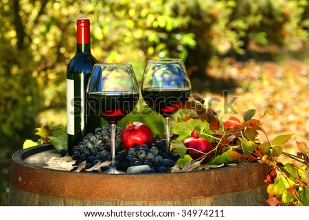Glasses of red wine on old barrel with autumn leaves - stock photo