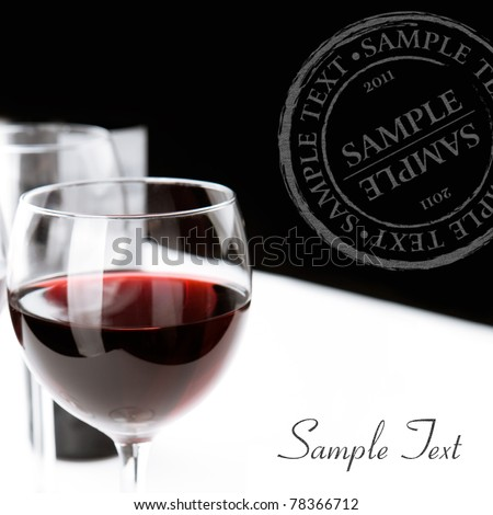 Glasses of red wine on white table cloth. Space for text isolated on white. Black background. - stock photo